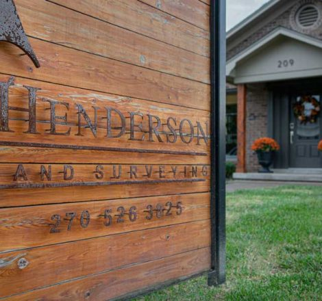 Wooden Henderson Land Surveying sign with metal lettering outside of the Morgantown, Kentucky office
